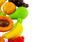 Colored jellys. Colored jelly candies in the shape of fruits banana pear grapes peach apricot lemon isolated on a white background Royalty Free Stock Photography