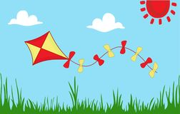Colored kite flies on background of summer sunny meadow. Colored kite flies on background of spring sunny meadow. Green grass against sky. Concept of freedom Royalty Free Stock Images