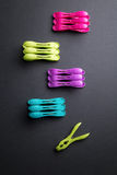 Colored laundry clips over a black background above view Royalty Free Stock Images