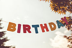 Colored letters Birthday on sky background Royalty Free Stock Photos