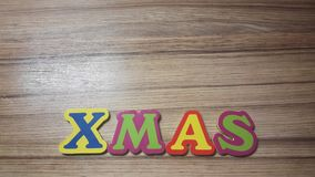 Colored letters form the word Xmas on wooden background Royalty Free Stock Photos