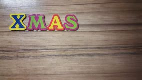 Colored letters form the word Xmas on wooden background Royalty Free Stock Images