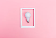 Colored lightbulb on a pink background. With frame Stock Photo