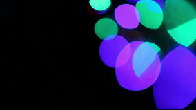 Colored lights bokeh on black stock footage