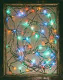 Colored lights festive Christmas garland in an old wooden frame Royalty Free Stock Photos