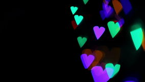 Colored lights heart bokeh on black stock video
