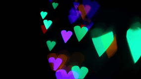 Colored lights heart bokeh on black stock footage