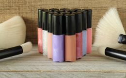 Colored lip gloss and makeup brushes stock photo