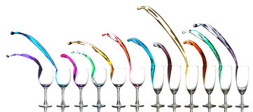 Colored liquid splashing out glasses. On a white background royalty free stock images