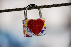 Colored locks hanging on the bridge for love. A mechanism for keeping a door, lid, etc., fastened, typically operated only by a key of a particular form royalty free stock image