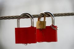 Colored locks hanging on the bridge for love. A mechanism for keeping a door, lid, etc., fastened, typically operated only by a key of a particular form stock photography