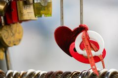 Colored locks hanging on the bridge for love. A mechanism for keeping a door, lid, etc., fastened, typically operated only by a key of a particular form stock image