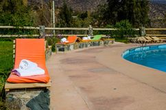 Colored loungers by the pool. Pool against the backdrop of the mountains. orange sun loungers. white towels royalty free stock photo