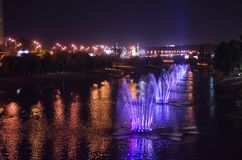 Colored luminous fountains in the middle of the lake at night. royalty free stock images