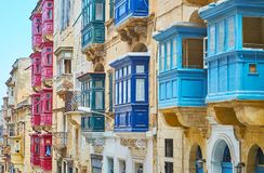 Colored Maltese balconies of Republic street, Valletta, Malta. The different colored scenic Maltese balconies, made of wood, decorate the facade walls of Stock Image
