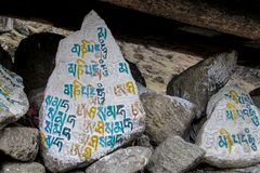 Colored Mani Stones with Buddhist mantra in Himalaya, Nepal. Old Mani Stones inscribed with a Buddhist mantra in the Himalaya region, Nepal. Nepali color letters royalty free stock images