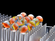 Colored Marbles. Stacked on aluminum fins Stock Photo