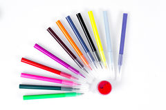 Colored markers laid out near the jars with paints like solar rays. Stationery on white background. Stock Photography