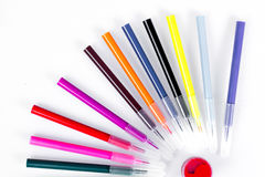 Colored markers laid out near the jars with paints like solar rays. Stationery on white background. Royalty Free Stock Photo