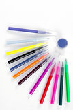 Colored markers laid out near the jars with paints like solar rays. Stationery on white background. Royalty Free Stock Photography