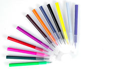 Colored markers laid out near the jars with paints like solar rays. Stationery on white background. Royalty Free Stock Image