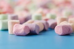 Colored marshmallow on plain blue background Royalty Free Stock Image