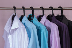 Colored men's shirts that hang on hangers. Colored men's shirts that hang on black hangers Stock Image