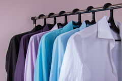 Colored men's shirts that hang on hangers. Colored men's shirts that hang on black hangers Royalty Free Stock Image