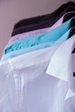 Colored men's shirts that hang on hangers. Colored men's shirts that hang on black hangers Stock Photo