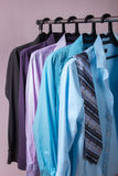 Colored men's shirts that hang on hangers. Colored men's shirts that hang on black hangers Stock Photos