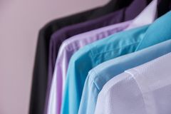Colored men`s shirts that hang on hangers. Colored men`s shirts that hang on black hangers on a pink background stock photo
