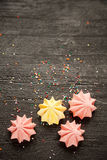 Colored meringue on a black background mock up. Meringues and confetti on a black wooden table Stock Images