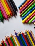Colored metalic clips, colored crayon row and note book with spiral, background and texture. School education, multicolor objects and white background stock image