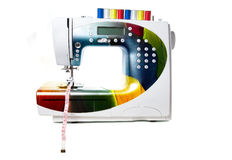 Colored modern sewing machine. With red, yellow, blue and white stitching on the top. Tape measure in foot. Isolated at white background stock photo