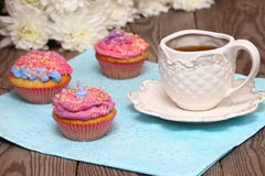Colored muffins with tea. Bright colored muffins with tea and flowers. Shallow DOF royalty free stock photography