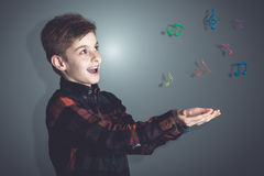 Colored Musical Notes Over the Hands of a Boy. Colored Musical Notes Over the Open Bare Hands of a Boy with Amazed Facial Expression Against Gray Gradient stock image