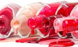 Colored nail polish. Bright-colored nail polish spilling from bottles Royalty Free Stock Photo