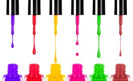 Colored nail polishes dripping from brush into bottle. Isolated on white background Stock Images