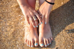 Colored nails. Foot and hands on the sand with colored nails Royalty Free Stock Images