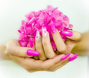 Colored nails for spring. Colored nails with pink flowers decorations to celebrate the spring and summer royalty free stock images