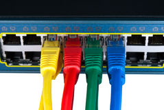 Colored Network Cables Connected to Switch. Rainbow colored ethernet network cables connected to a switch isolated on white background. Top view Royalty Free Stock Photo
