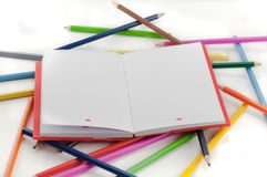 Colored notebook and pencils on white background Stock Image