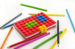 Colored notebook and pencils on white background Royalty Free Stock Photography