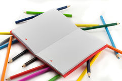 Colored notebook and pencils on white background Stock Images