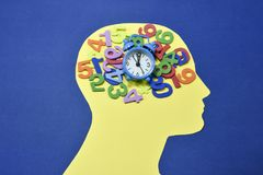 Colored numbers and alarm clock on male head contour. Different colored numbers and small bell ring alarm clock , running and placed on an yellow male head Stock Photography