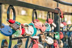 Colored old wedding locks in the shape of a heart hang on the forged railing of the bridge, a symbol of the long and happy life of. The newlyweds stock photography