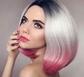 Colored Ombre bob hair extensions. Manicure nails. Beauty makeup. Attractive Model Girl blonde with short pink hairstyle isolated on gray background. Closeup Stock Image