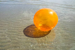 Colored orange ball in water on beach Stock Photography
