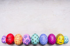 Colored ornamental eggs for Easter with painted faces border ,place for text  wooden rustic background top view close up. Colored ornamental eggs for Easter with Stock Photos