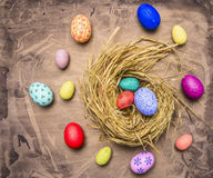 Colored ornamental eggs for Easter with painted faces lie in a nest wooden rustic background top view close up Royalty Free Stock Photos